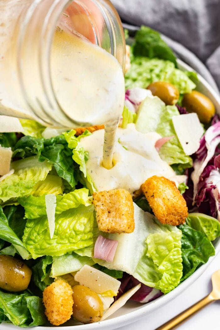 Creamy Italian dressing being poured over a salad with croutons and parmesan cheese.