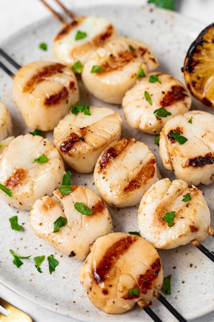 Grilled scallops on a plate topped with chopped parsley and a lemon on the side.
