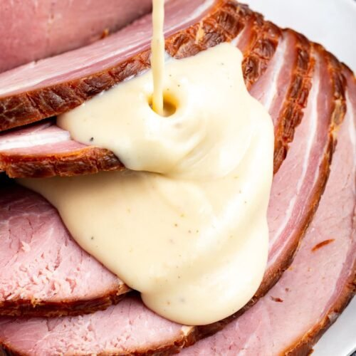 Sliced ham with ham gravy being poured over the top.