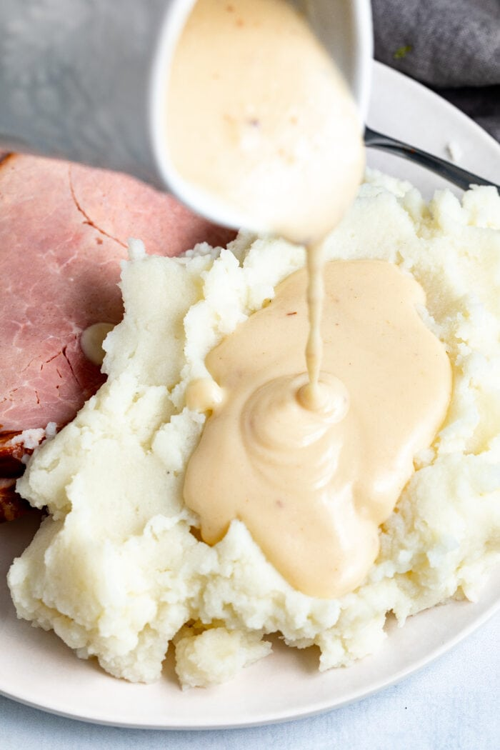 Ham gravy poured over mashed potatoes with sliced ham on the side.