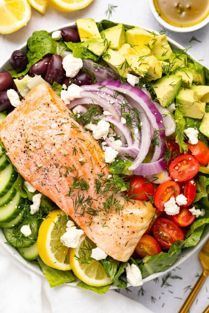 Salmon filet over salad with lemon and dressing on the side.