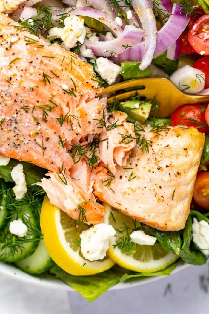 fork cutting into a salmon filet over salad.