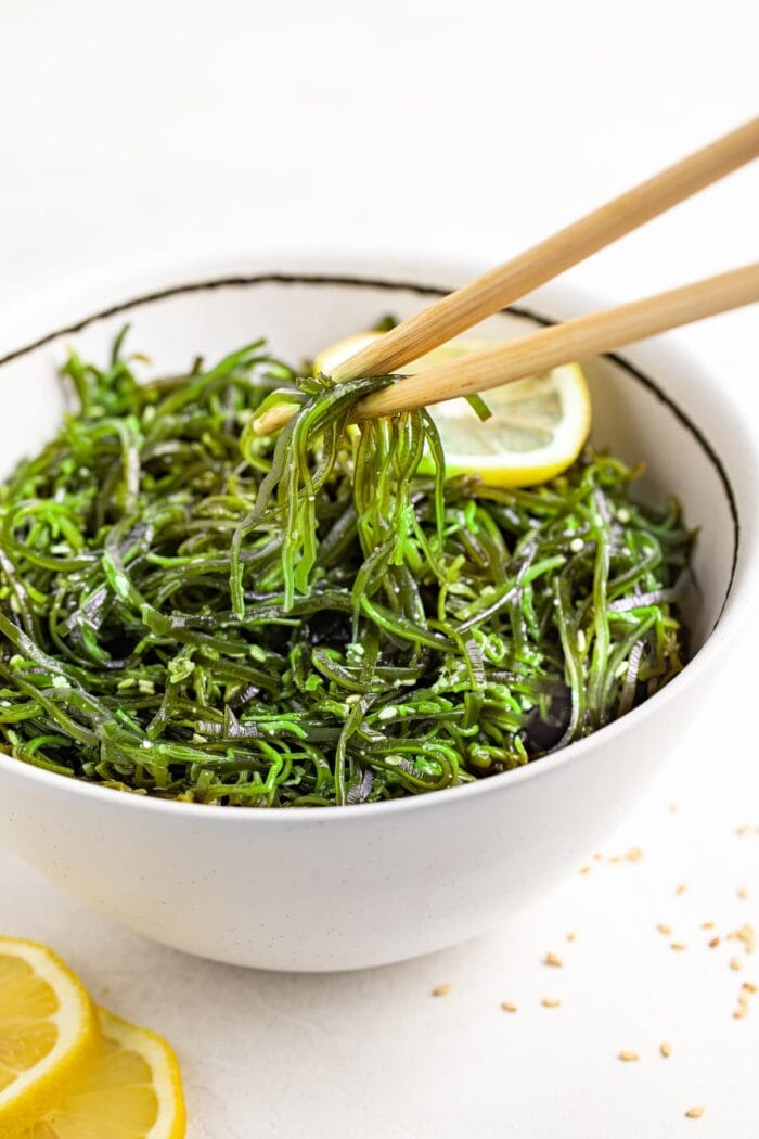 seaweed salad being lifted out of a bowl with chopsticks