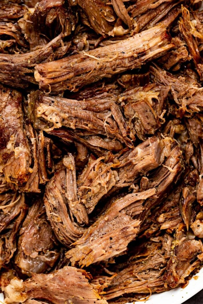 Close up image of shredded beef in a bowl.