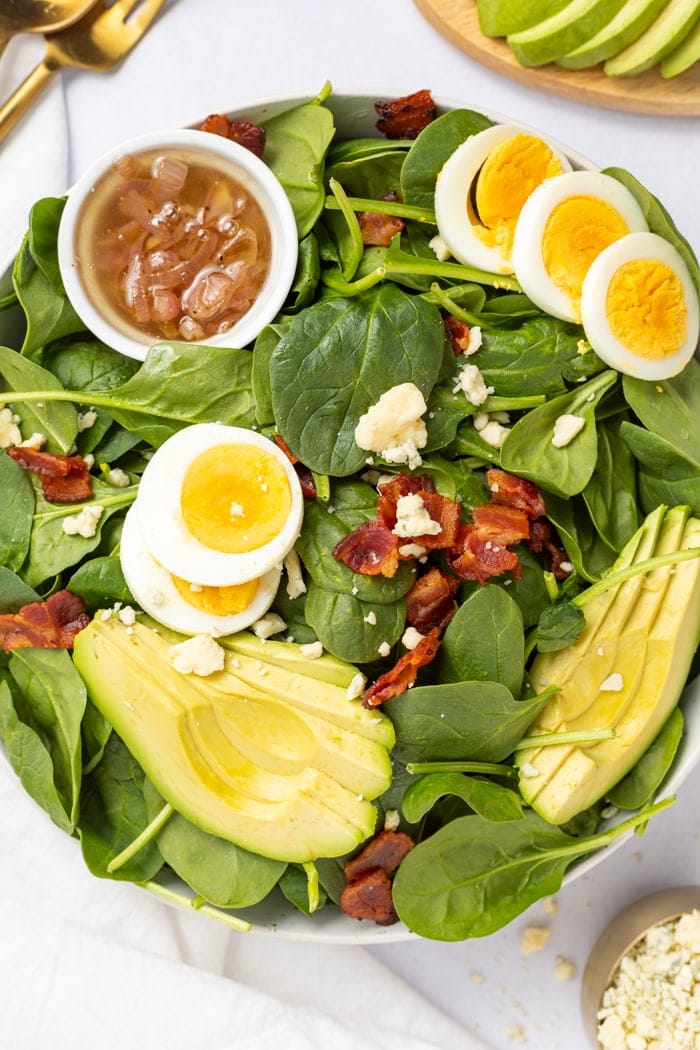 Spinach Salad overhead shot with a hot bacon dressing on the side.