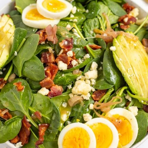 Spinach Salad with Hot Bacon Dressing in a bowl topped with hard boiled eggs, avocado, gorgonzola cheese, and crispy bacon.