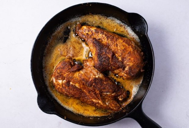 Blackened chicken breasts in cast iron skillet with melted butter