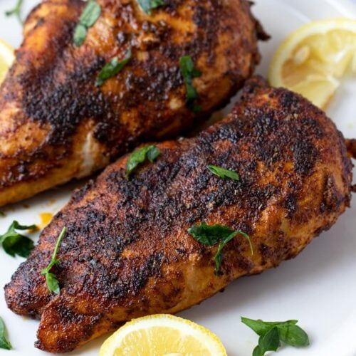 Blackened chicken on a white plate with lemon wedge garnish - easy chicken recipes for dinners with few ingredients