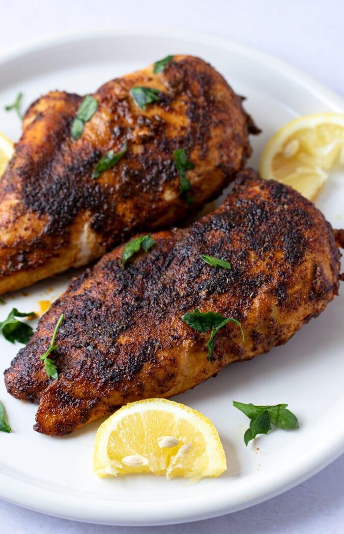 Blackened chicken on a white plate with lemon wedge garnish