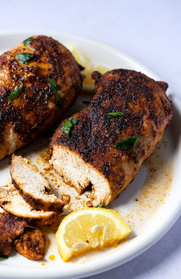 Blackened chicken on a white plate, sliced to show meat inside