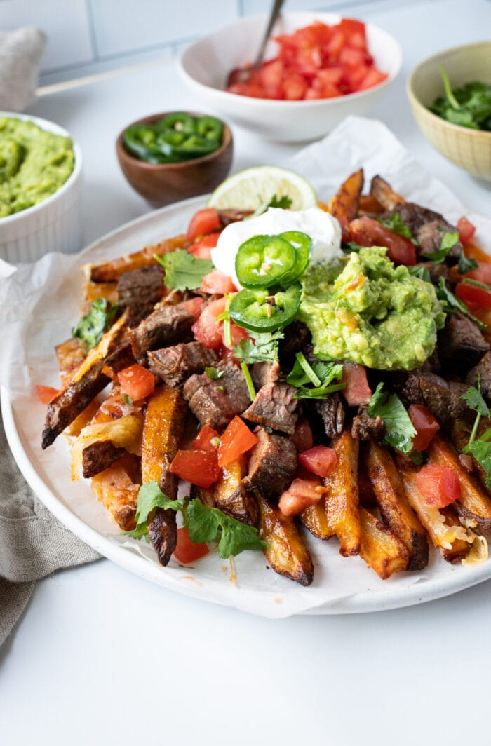 Carne asada fries on a plate with sour cream and guacamole