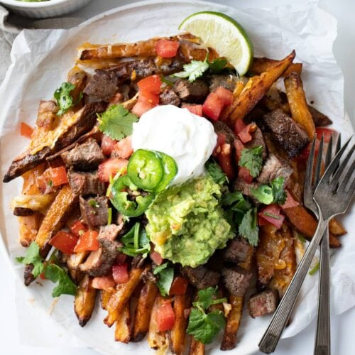 Overhead angle of carne asada fries on a plate with sour cream and guacamole