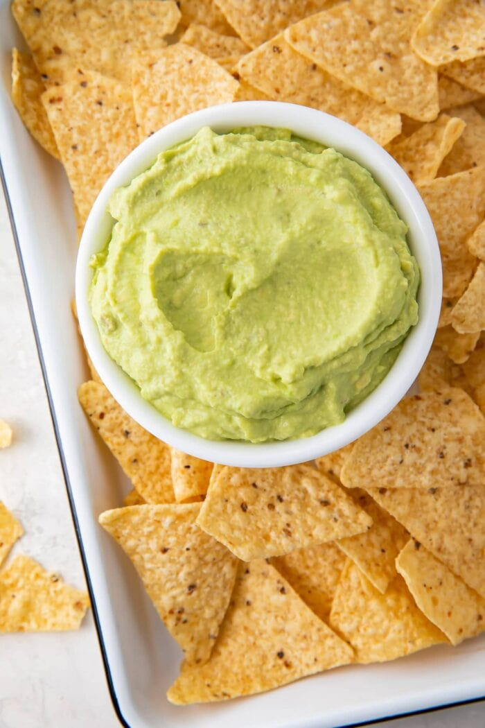 Guacamole dip in a bowl on a platter with tortilla chips