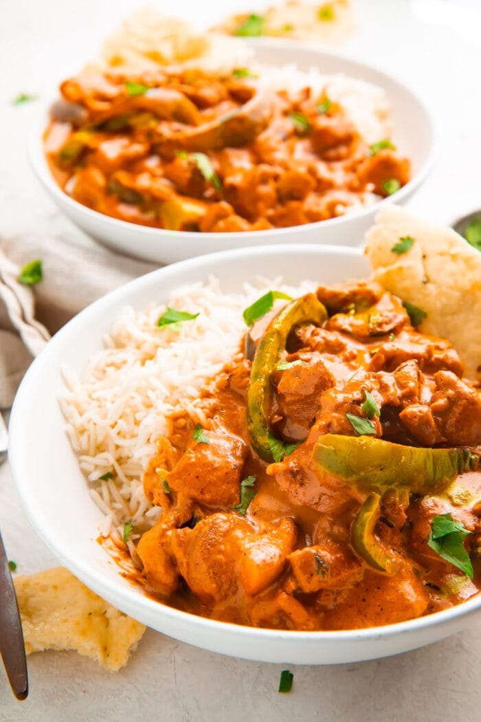 Angled photo of Instant Pot chicken tikka masala in a bowl with basmati rice and naan