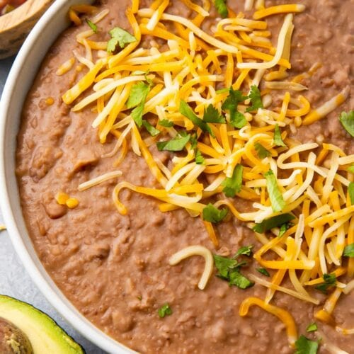 Instant Pot refried beans in a bowl topped with shredded cheese