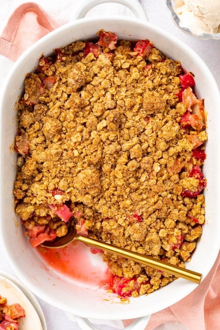 Overhead picture of rhubarb crumble in baking dish with a scoop removed and ice cream on the side.