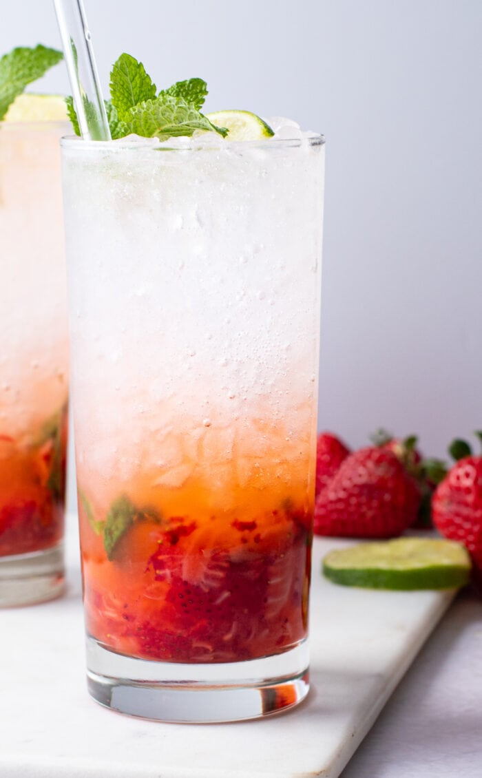 Strawberry mojito in a tall glass with ice topped with mint leaves