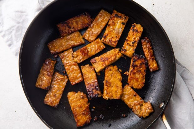 Marinated tempeh bacon in large skillet