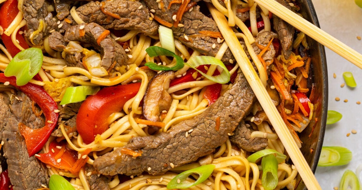 beef lo mein in a skillet with slice green onion and sesame seeds on top