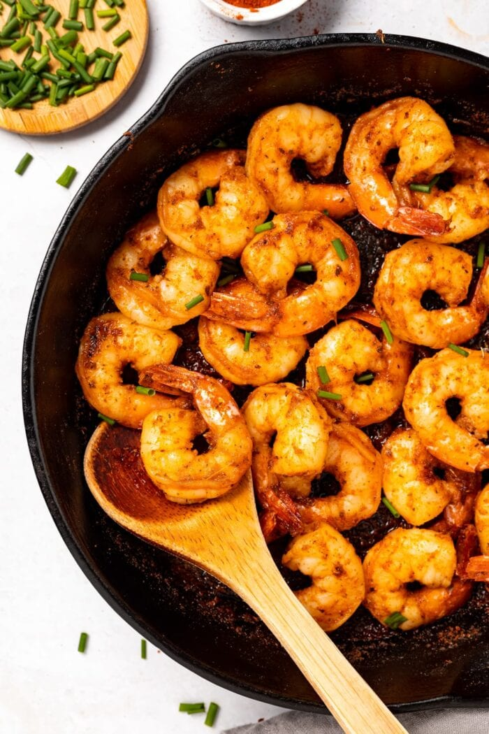 Cajun shrimp in a skillet with chives on the side.