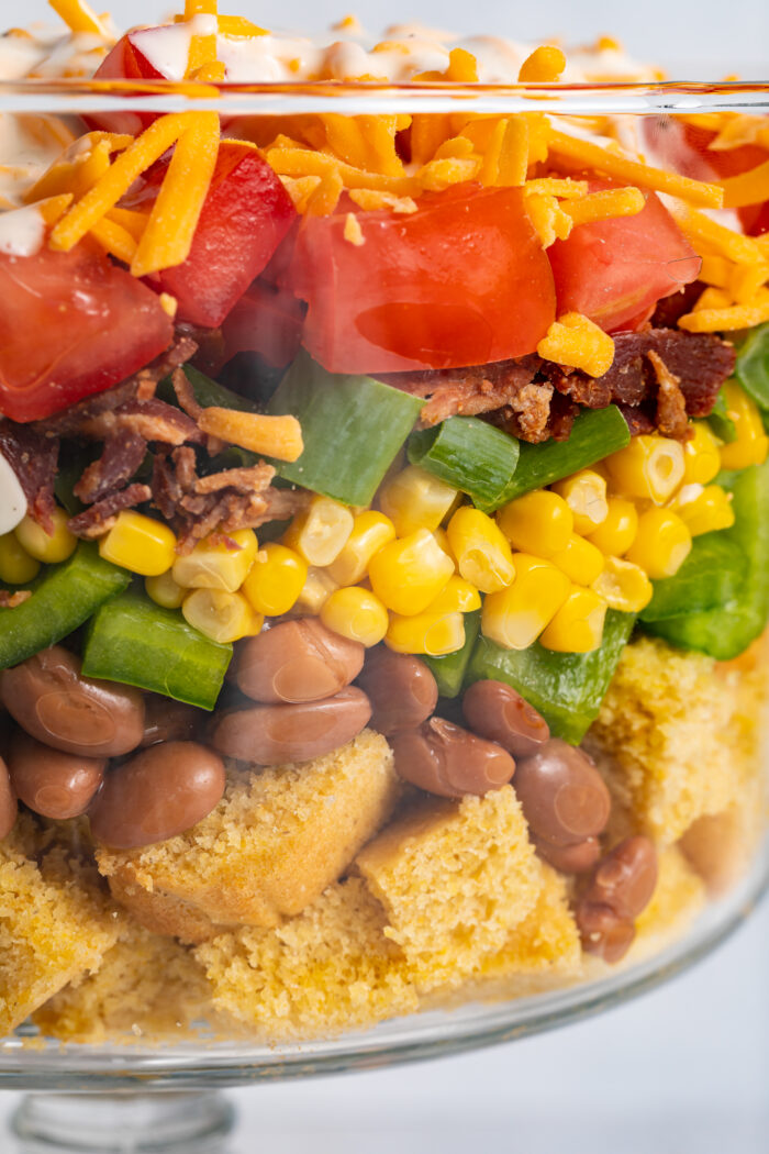 Close up image of cornbread salad layered in a dish.