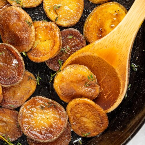 crispy pan fried potatoes being lifted out of a pan with a spoon