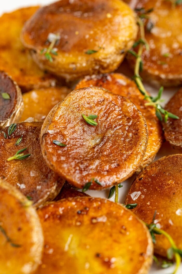 close up image of crispy pan fried potatoes sprinkled with fresh thyme
