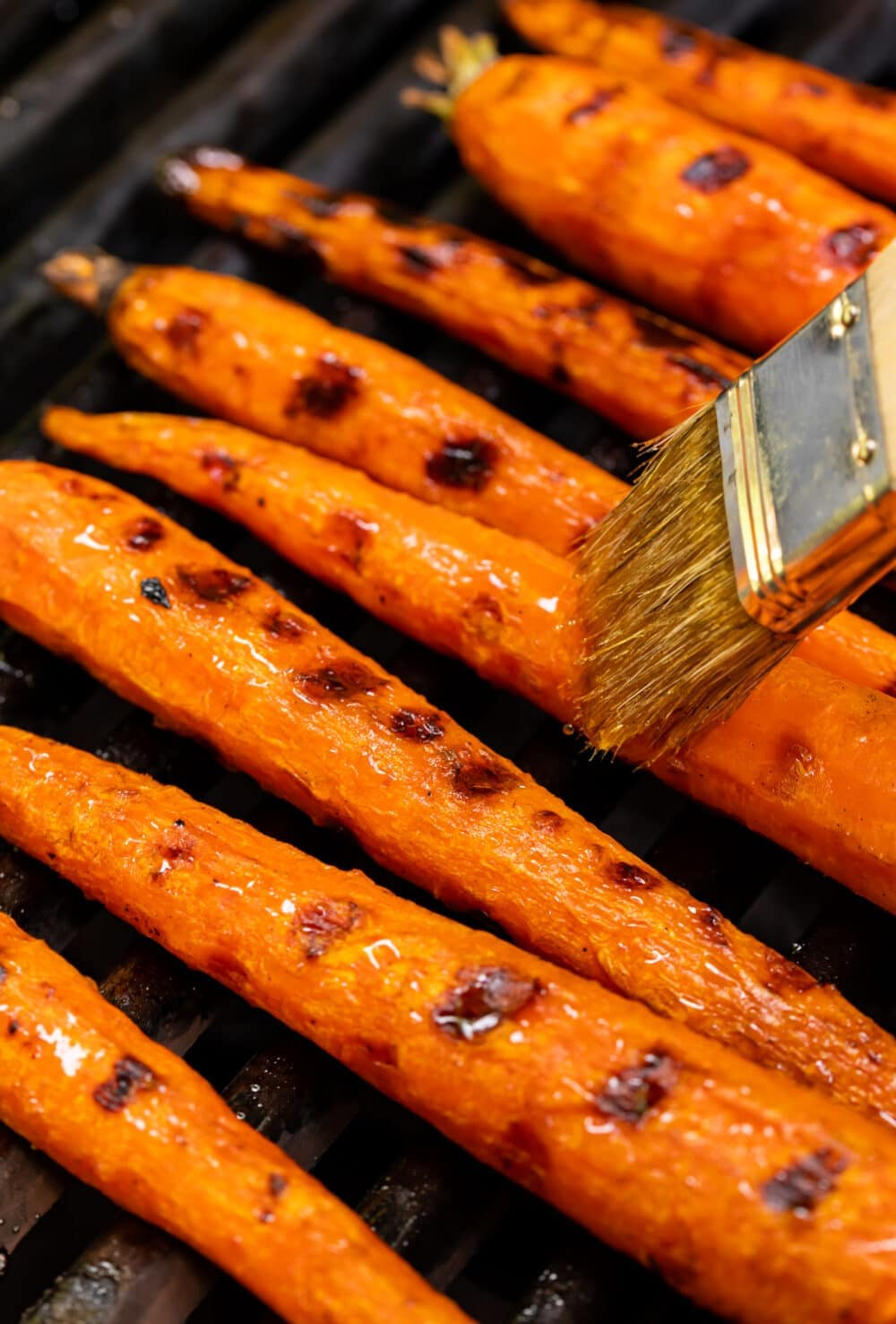 maple syrup being brushed on maple glazed grilled carrots
