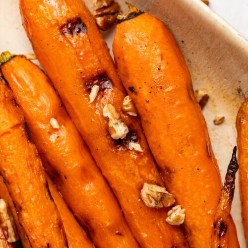 maple glazed grilled carrots in a serving dish with chopped pecans on top