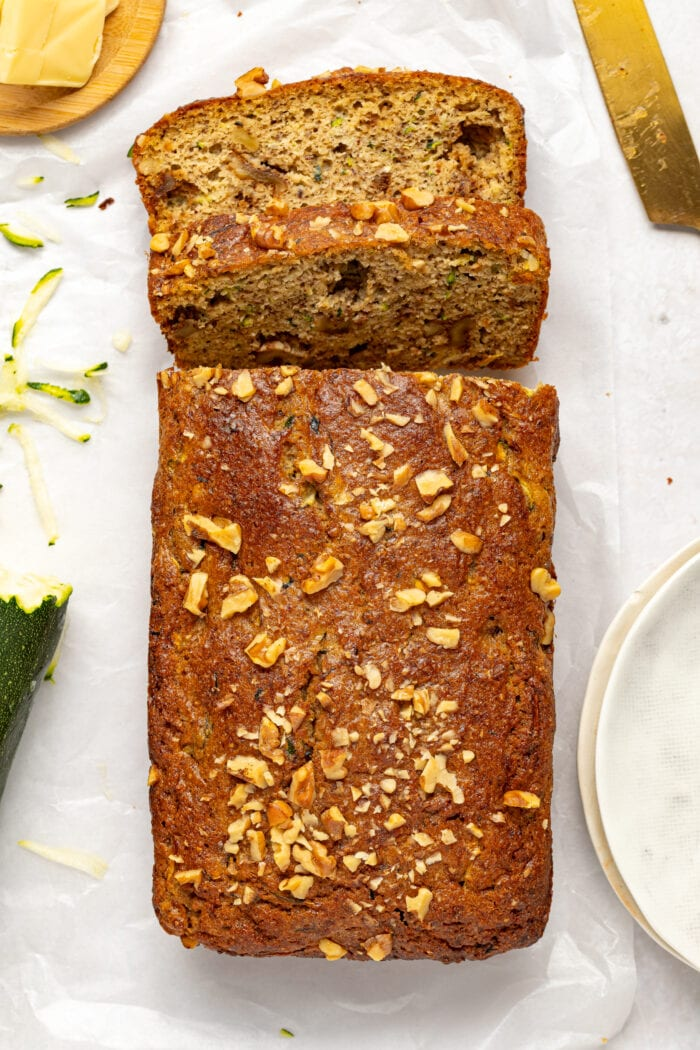 overhead image of keto zucchini bread surrounded by butter, shredded zucchini and a knife