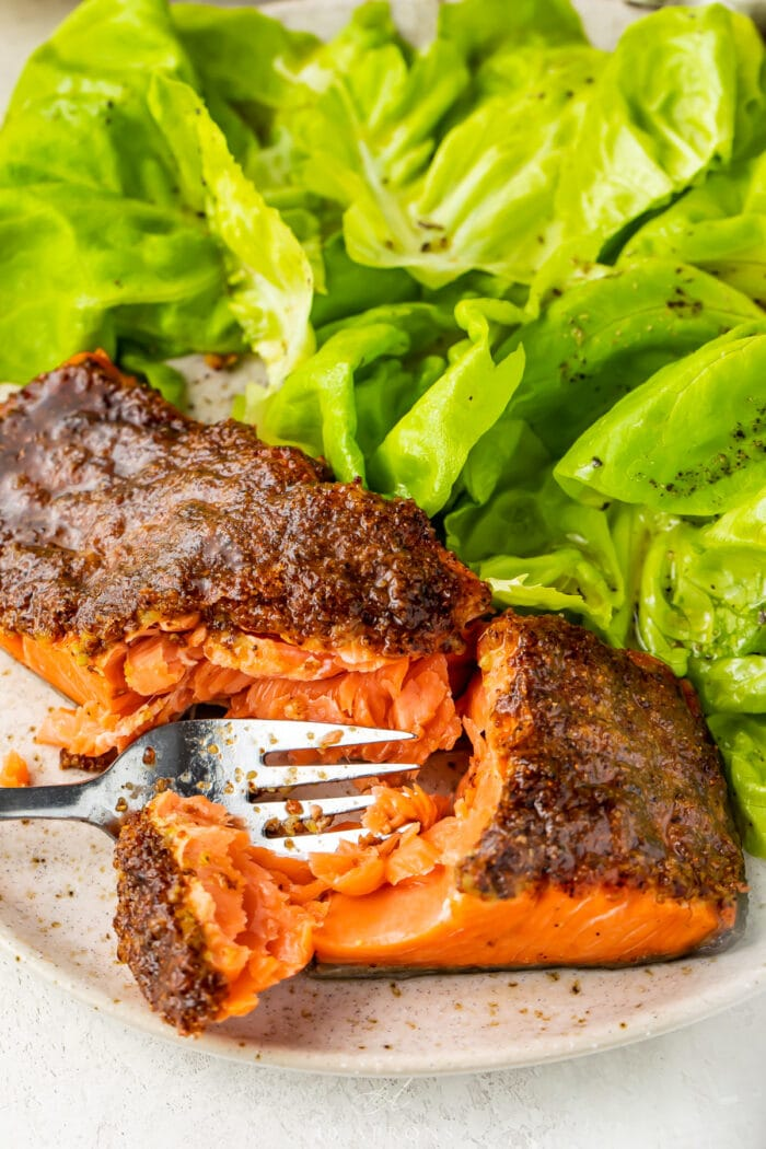 A fork cutting through flaky air fryer salmon on a plate with a small green salad