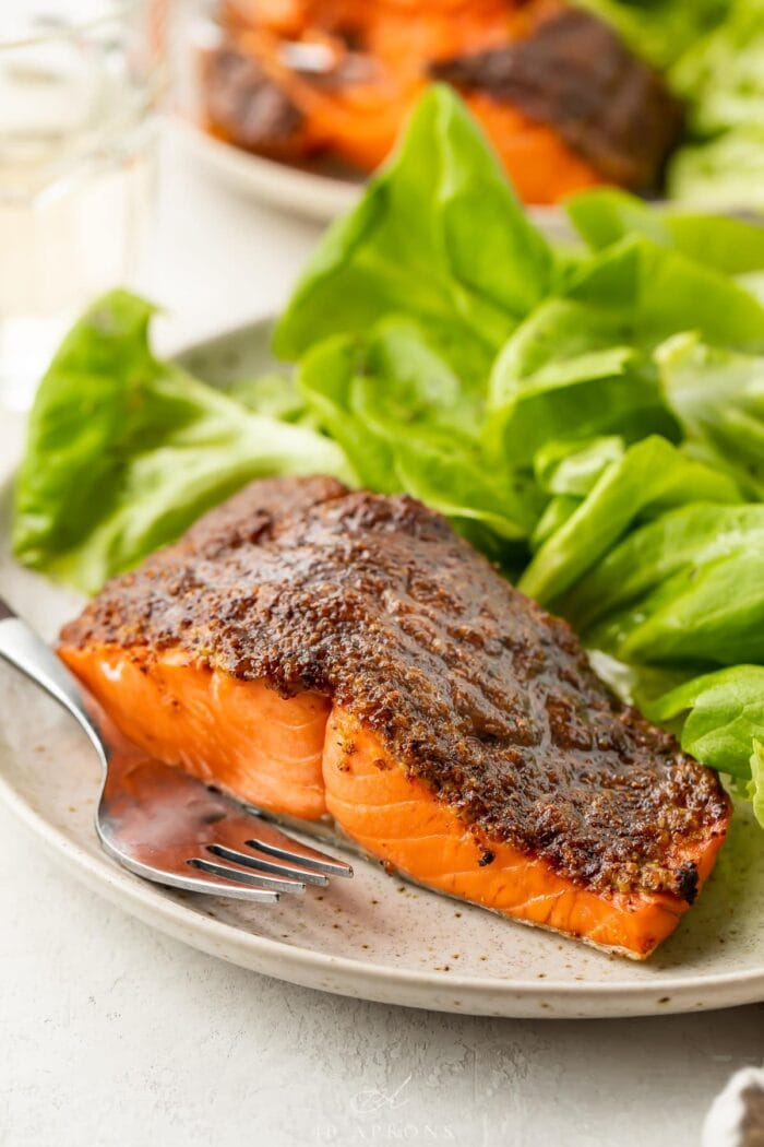Air fryer salmon on a plate next to a small green salad
