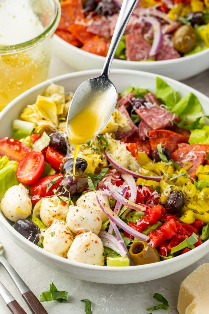 Italian vinaigrette spooned over an antipasto salad in a large bowl