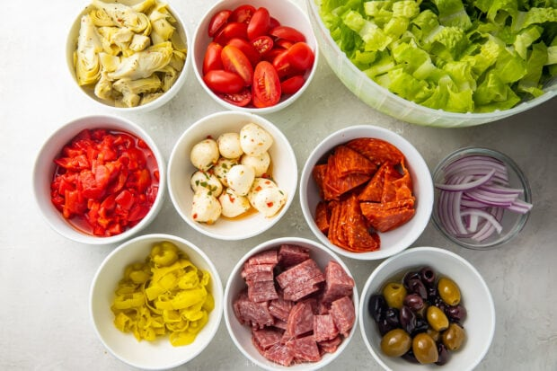 Ingredients for antipasto salad separated into small white bowls