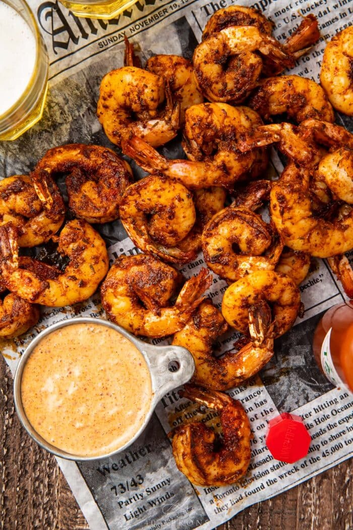 A pile of blackened shrimp on newspaper next to a dipping cup of remoulade sauce