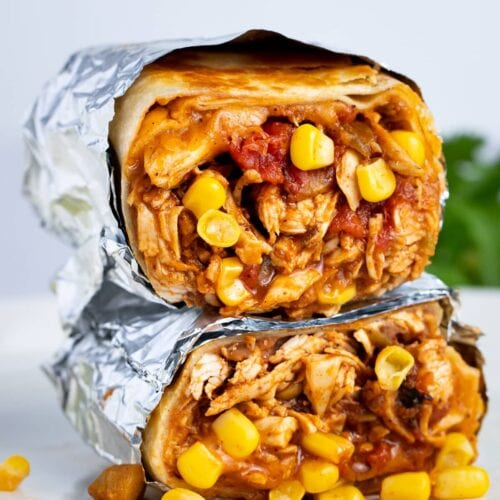 Two chicken burritos stacked on top of each other, cut crosswise to show chicken, corn, refried beans, and tomatoes inside