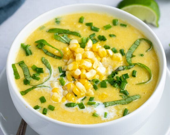 Corn soup in a white soup bowl on a white plate, sitting on a marble tabletop with lime wedges and a blue napkin in the background