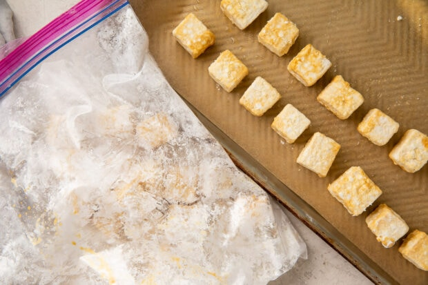 Coated tofu cubes in a zippered plastic bag next to a baking sheet lined with tofu cubes