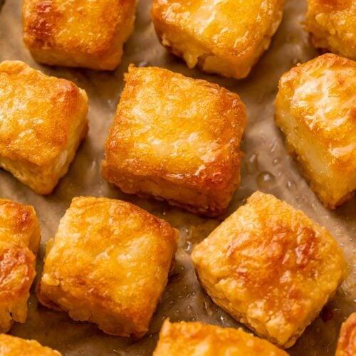 Close up photo of crispy baked tofu squares on a baking sheet