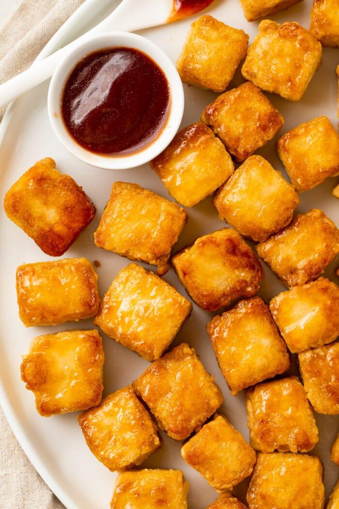 Crispy baked tofu cubes on a white plate