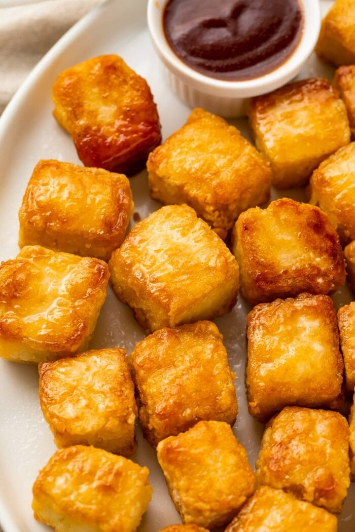 Close up view of crispy baked tofu cubes on a white plate