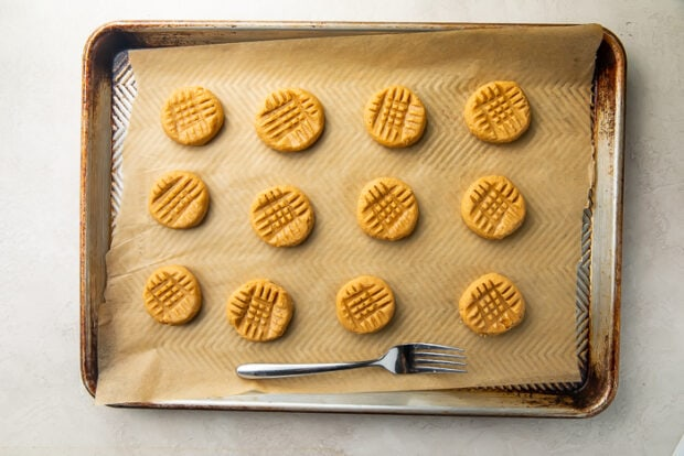 Gluten free peanut butter cookies on baking sheet lined with parchment paper next to fork used to make criss-cross pattern on top of cookies