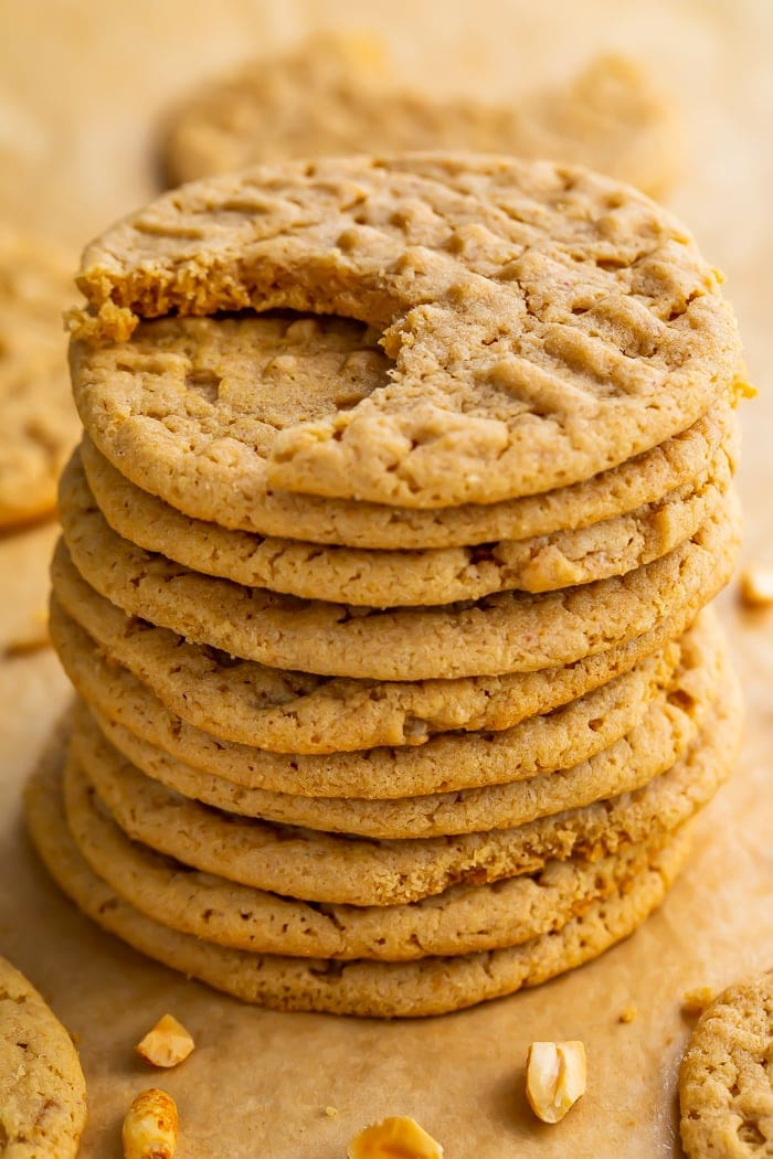 Stack of round gluten free peanut butter cookies on parchment paper. Top cookie has one bite missing.
