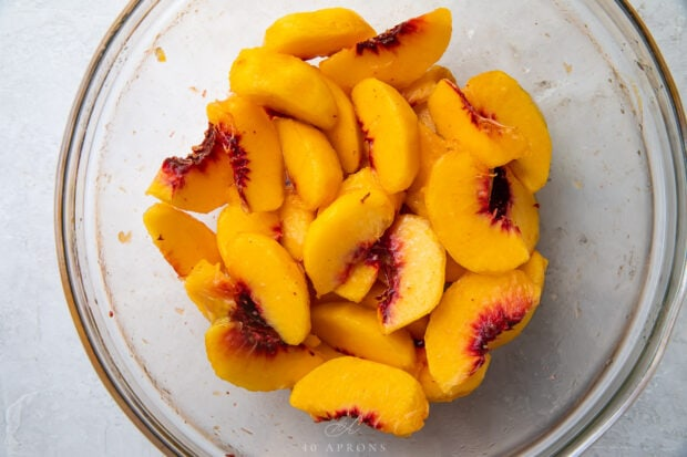 Peach slices in a glass mixing bowl with lemon juice