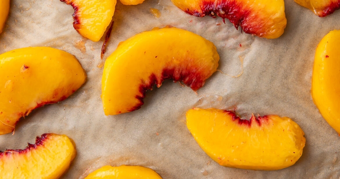 Peach wedges on a baking sheet lined with parchment paper