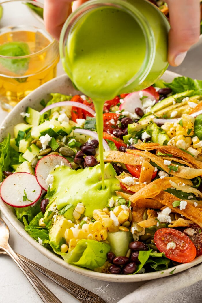 Cilantro lime dressing poured over Mexican salad in a white bowl