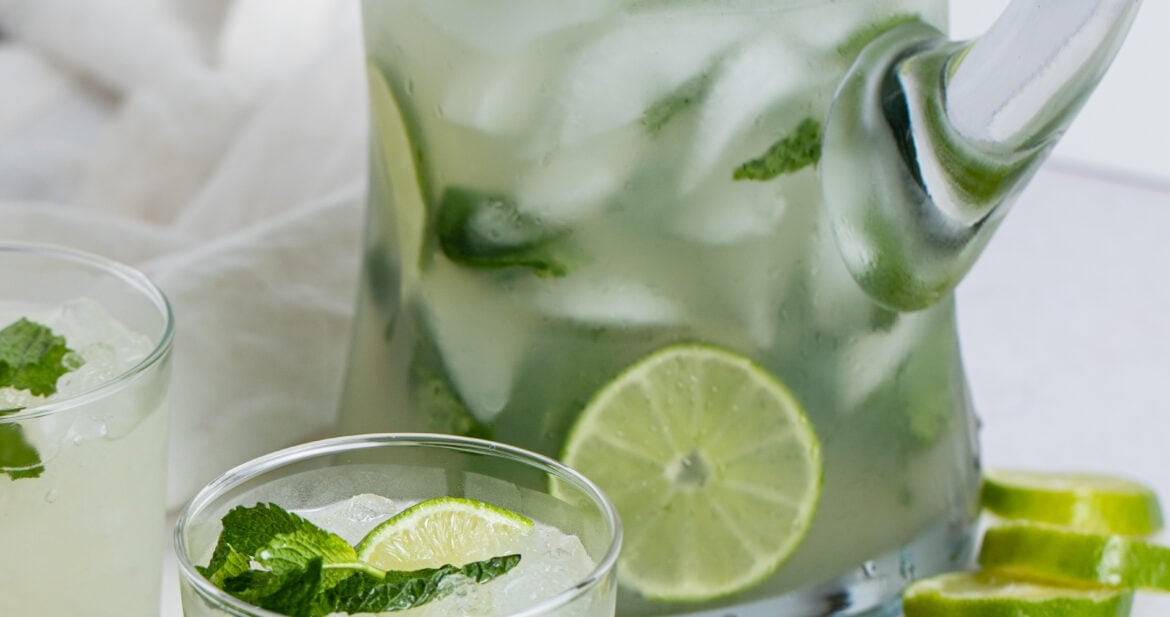 Mojito in a glass next to a tall pitcher of mojitos, garnished with mint leaves and limes