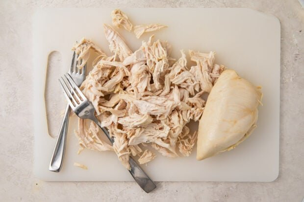 Shredded chicken breasts on a cutting board with 2 forks, next to whole cooked chicken breast