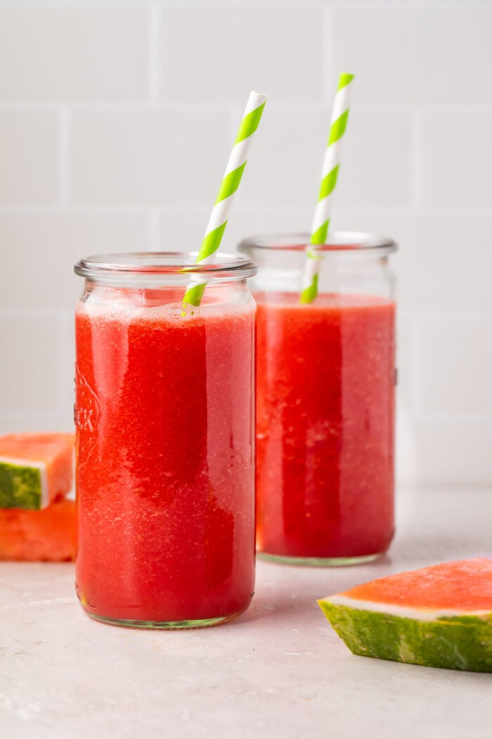 Two glasses of watermelon juice with green and white striped straws