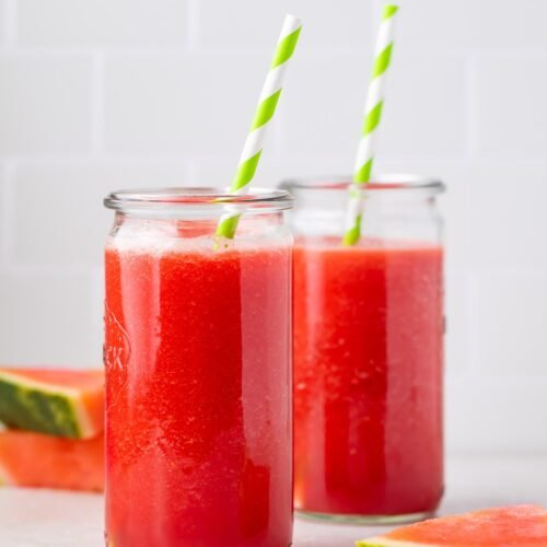 Zoomed out photo of two glasses of watermelon juice in front of slices of watermelon